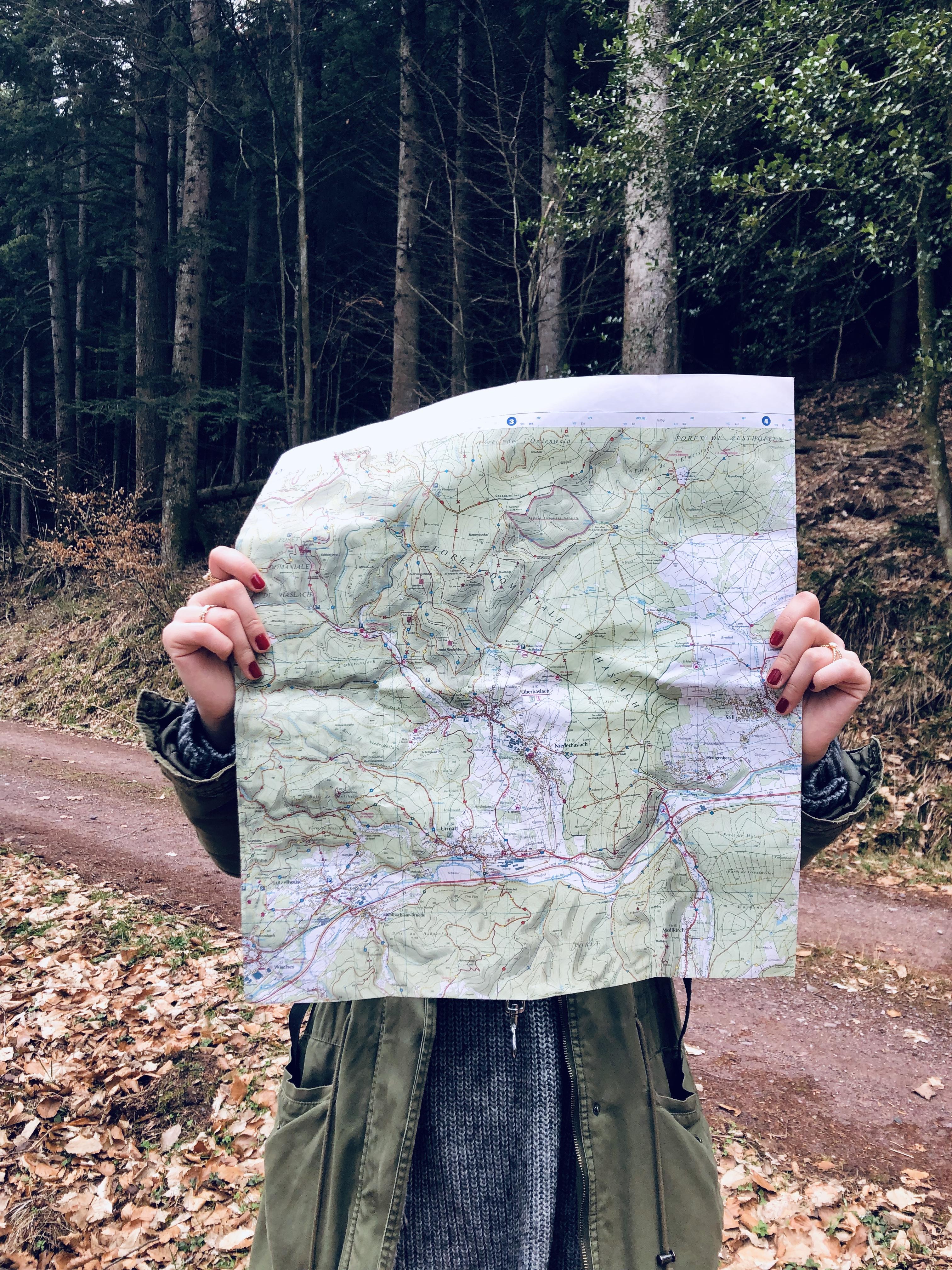 Une jeune femme tient une carte IGN des Vosges devant elle