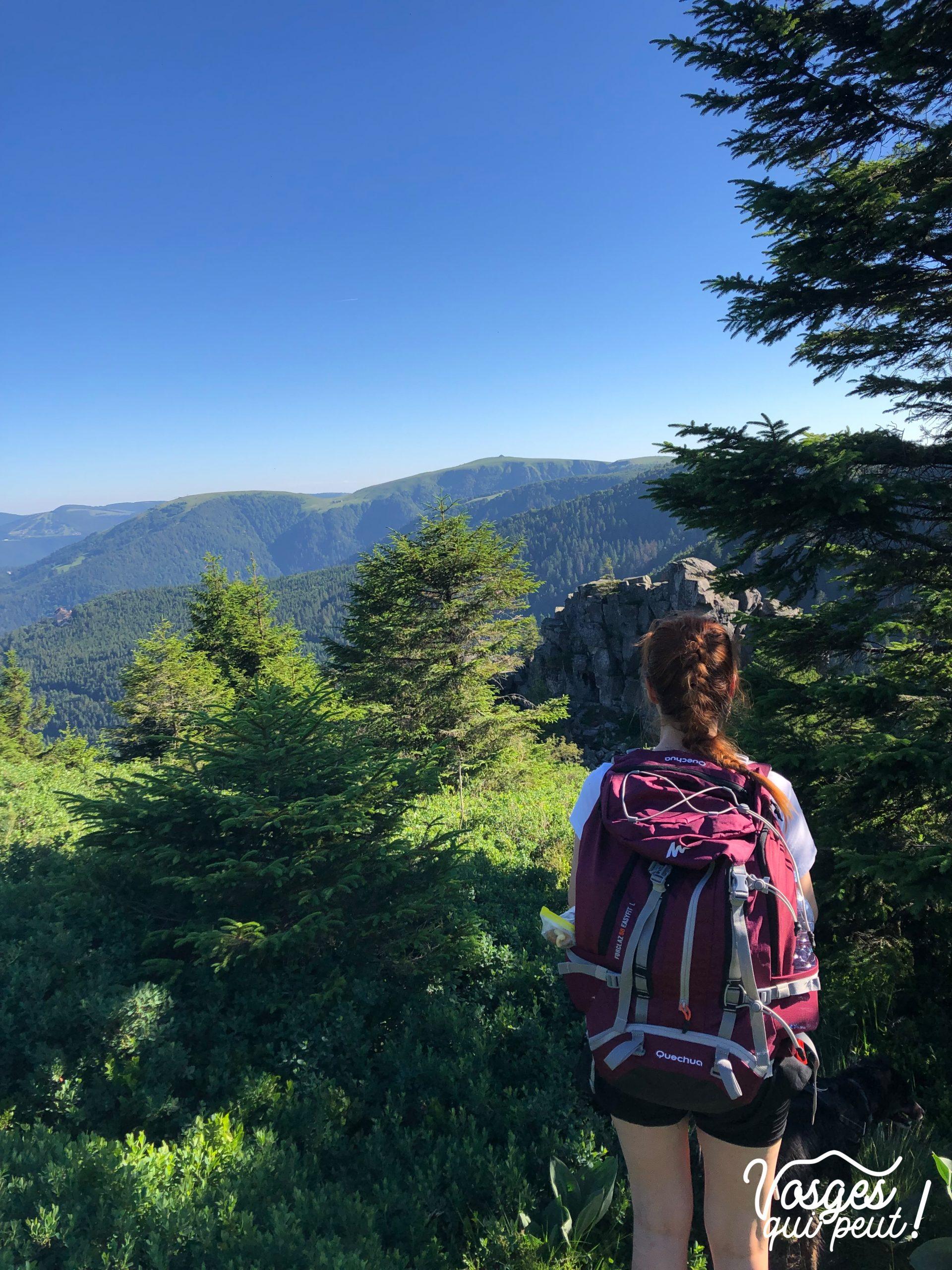 Une randonneuse devant un rocher dans les Vosges