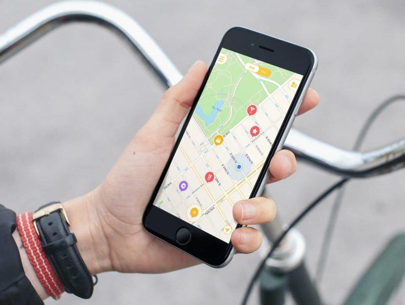 une main tient un téléphone avec l'application mapstr ouverte