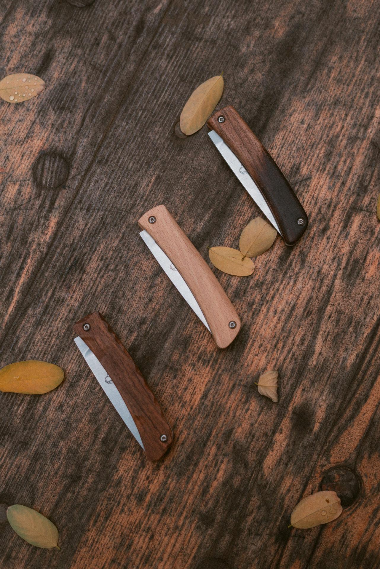 trois couteaux sur une table en bois