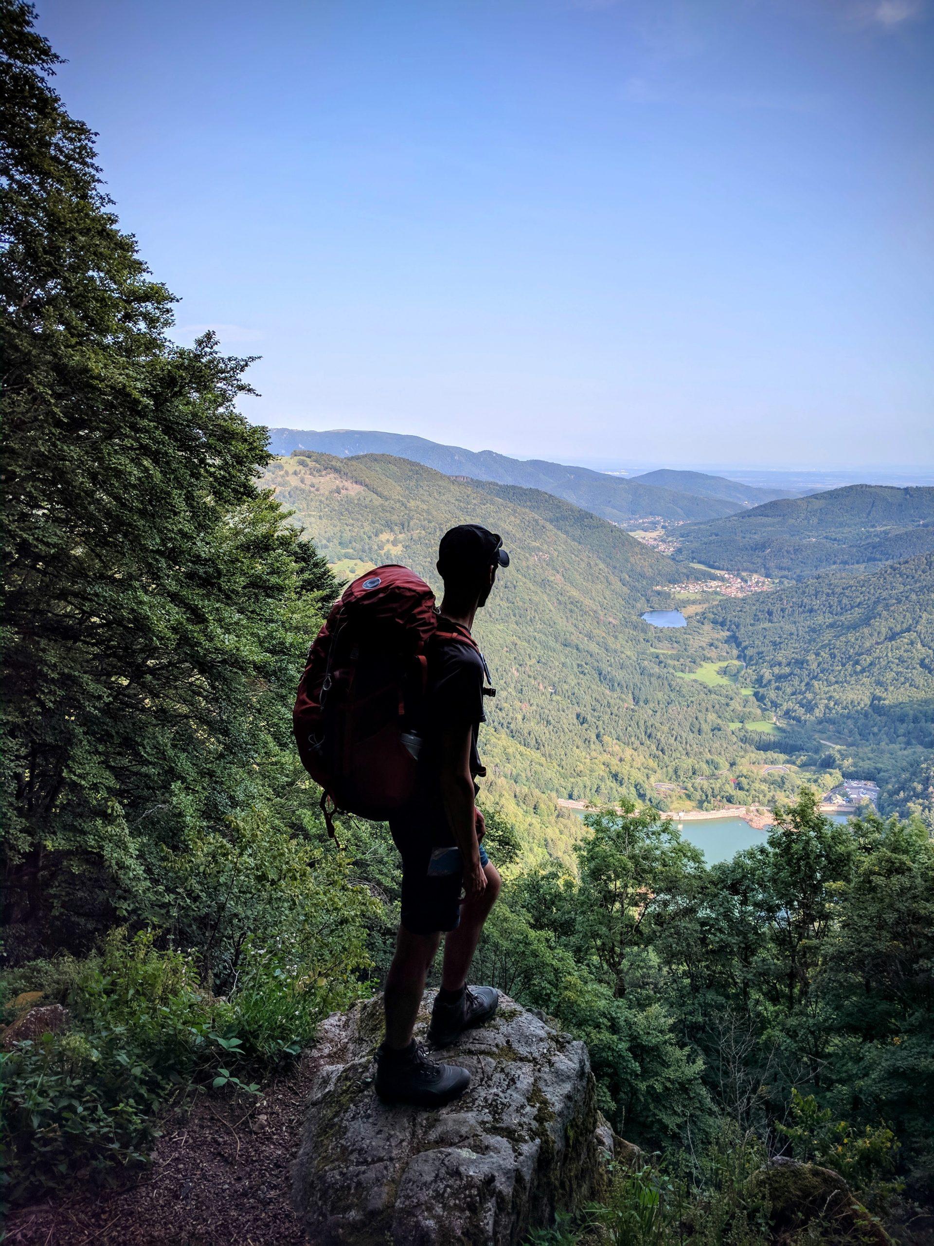 Un randonneur se tient debout sur un rocher devant la vallée de Masevaux en Alsace