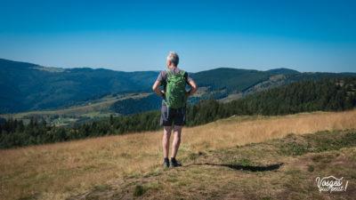 Un randonneur vu de dos regarde les Vosges pendant une randonnée en Alsace