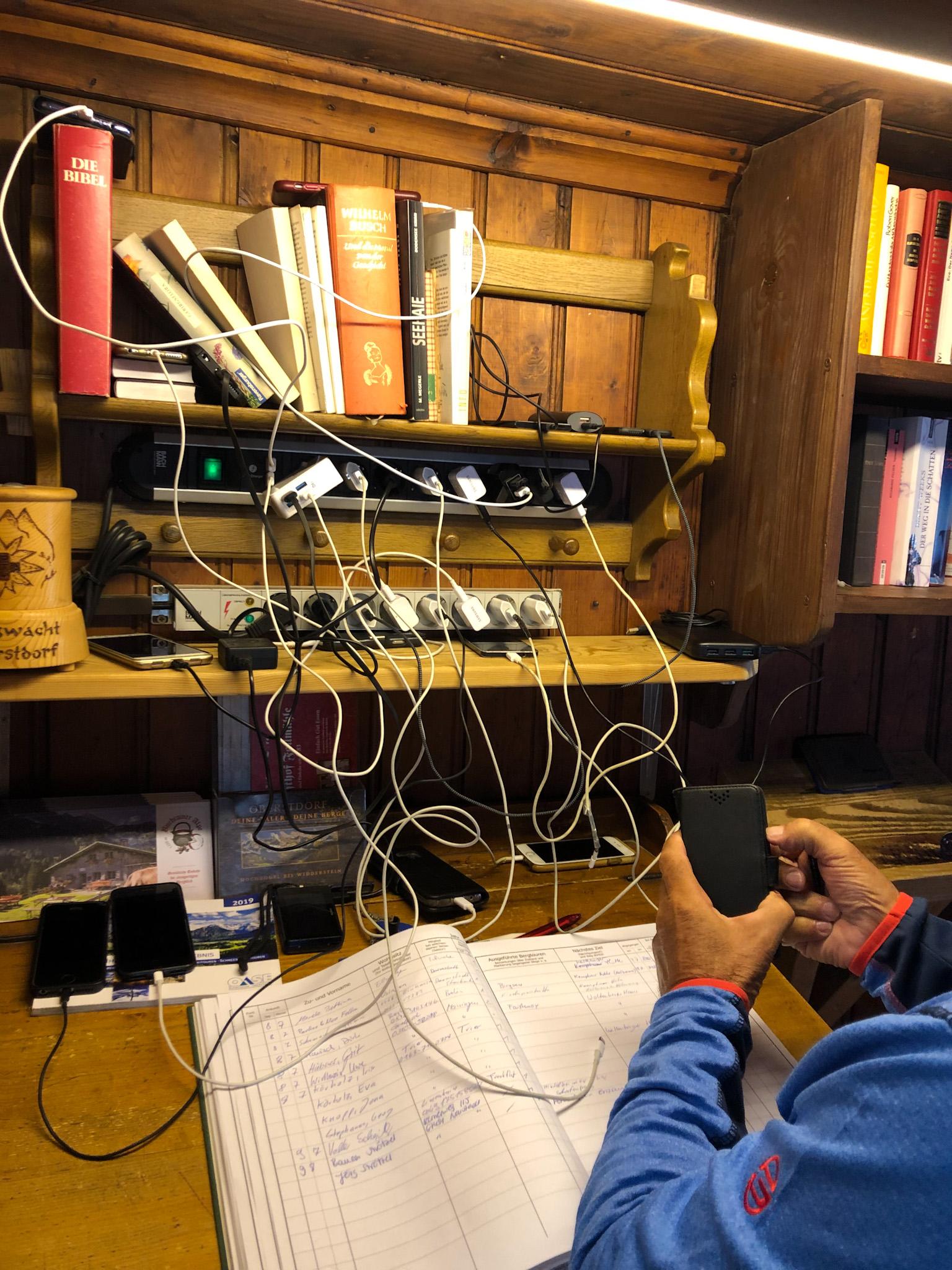Un homme charge son téléphone sur une multiprise encombrée au refuge de Rappensee dans les Alpes d'Allgäu en Bavière