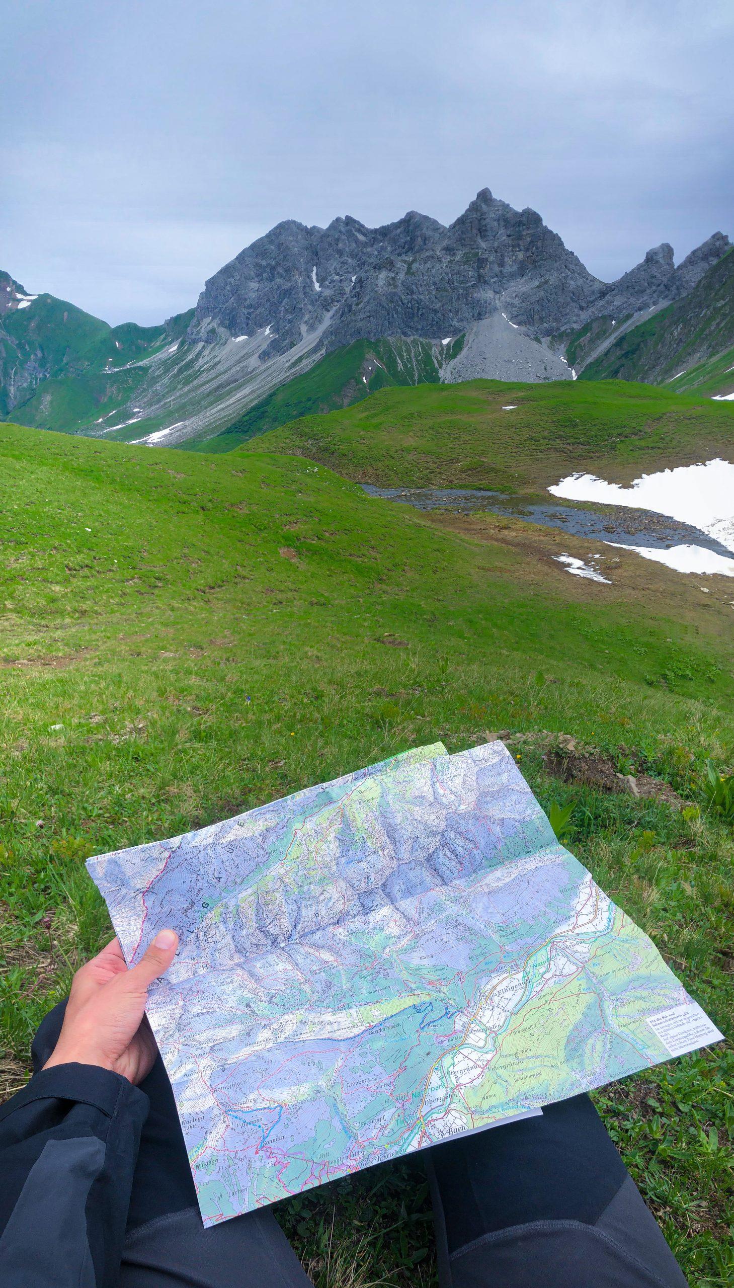 Un randonneur tient entre ses mains une carte de randonnée dans les Alpes d'Allgäu en Bavière