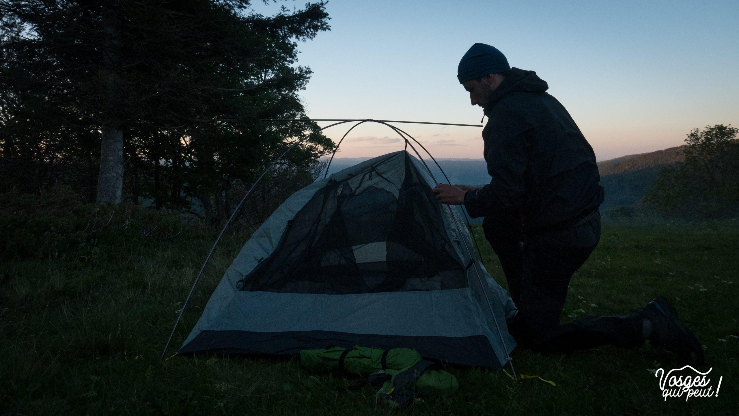 Un randonneur monte sa tente pour un bivouac dans les Vosges