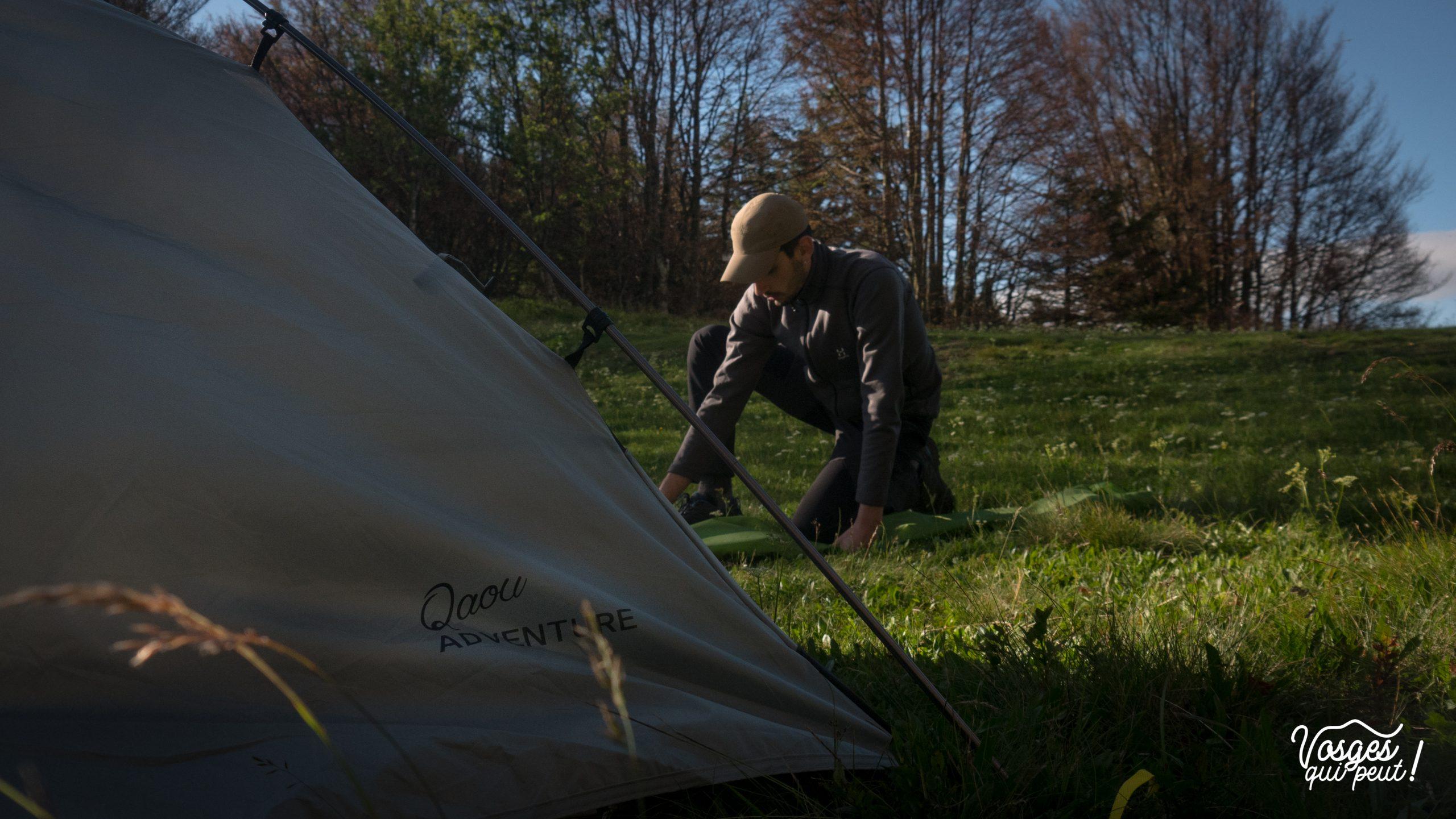Randonneur montant sa tente pour un bivouac dans les Vosges