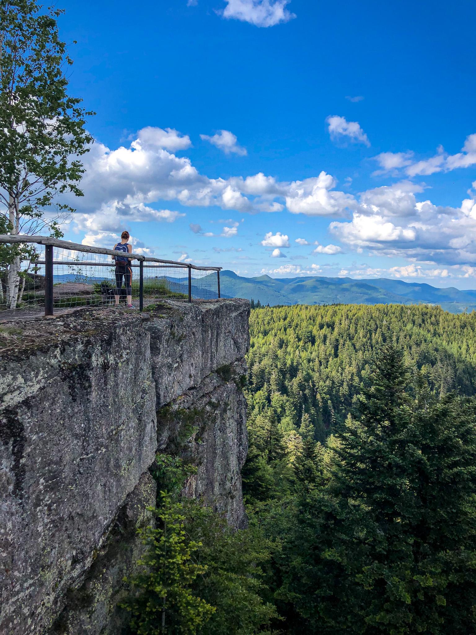 Une randonneuse admire le paysage depuis la Chatte Pendue dans la Vallée de la Bruche