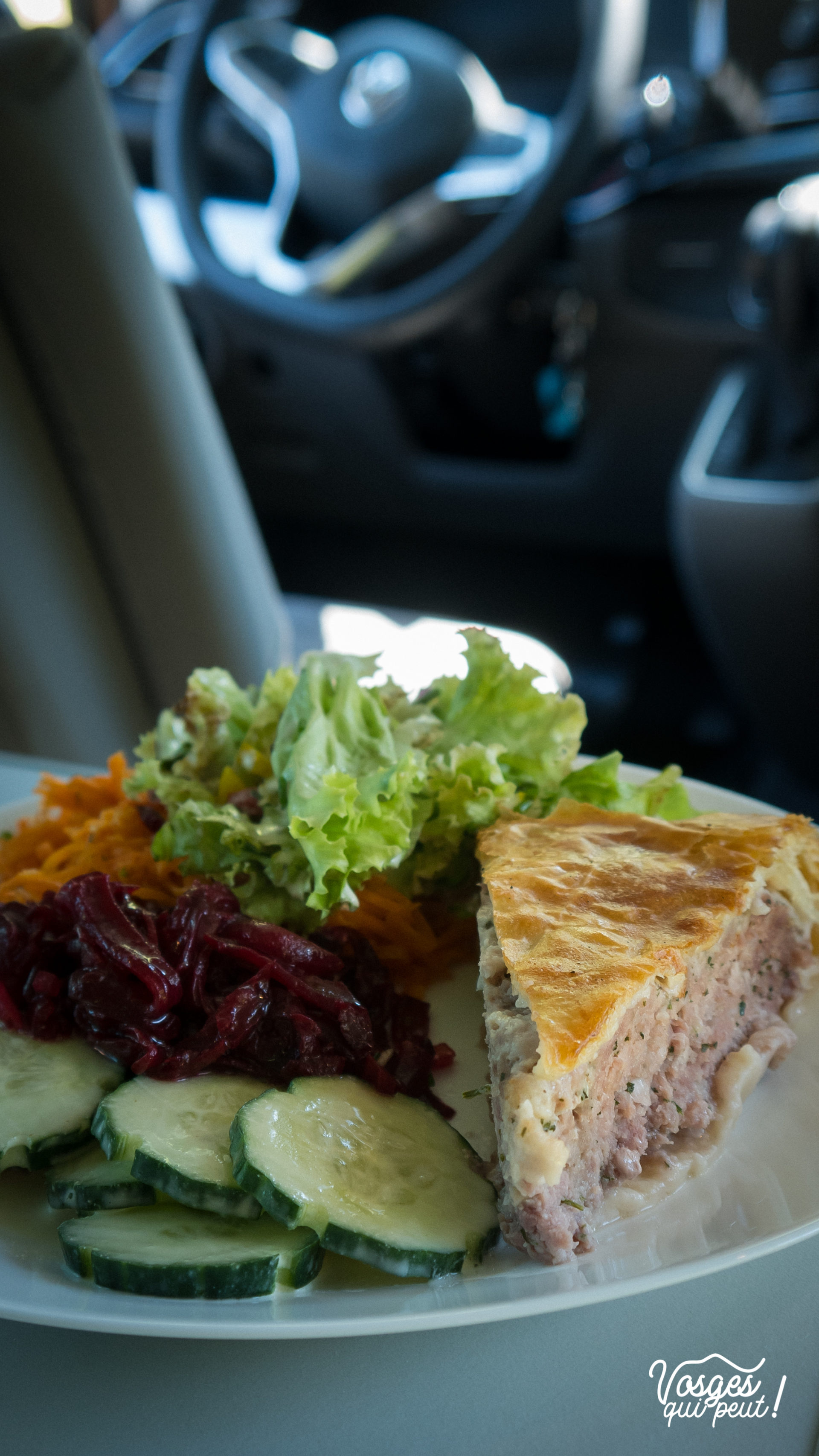 Une tourte à la viande et ses crudités, servies dans une assiette dans un van aménagé WeVan