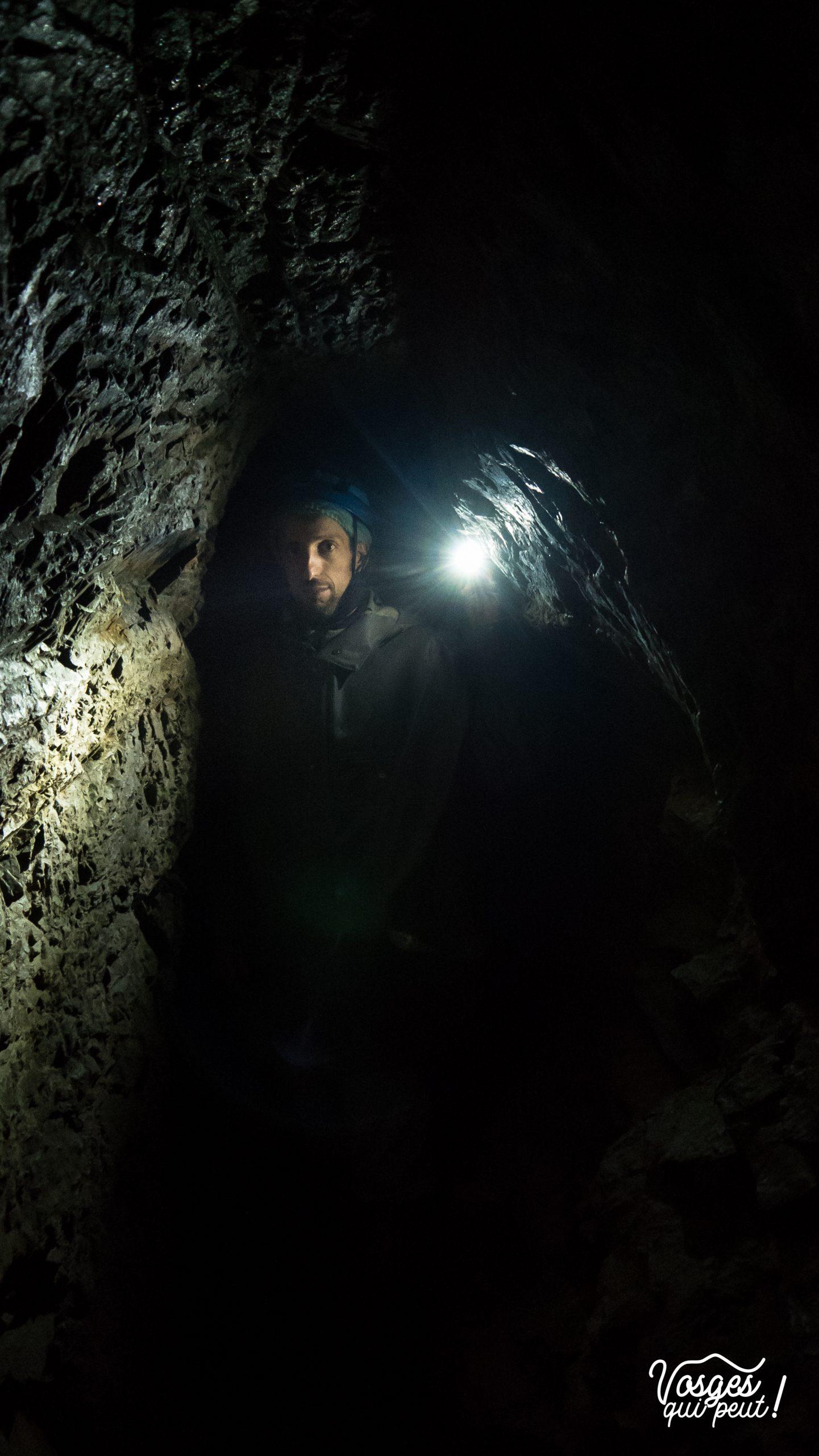 Un homme tient une lampe à l'intérieur d'une galerie de mine dans la vallée de Sainte-Marie-aux-Mines
