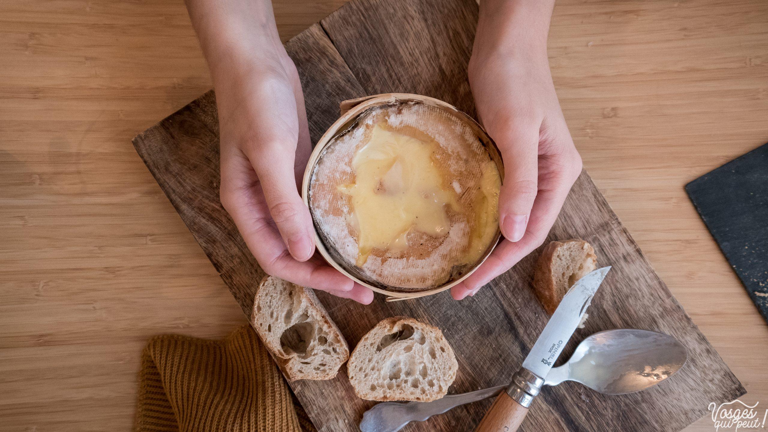 Un Mont d'Or au four posé sur une planche en bois accompagné de morceaux de pain