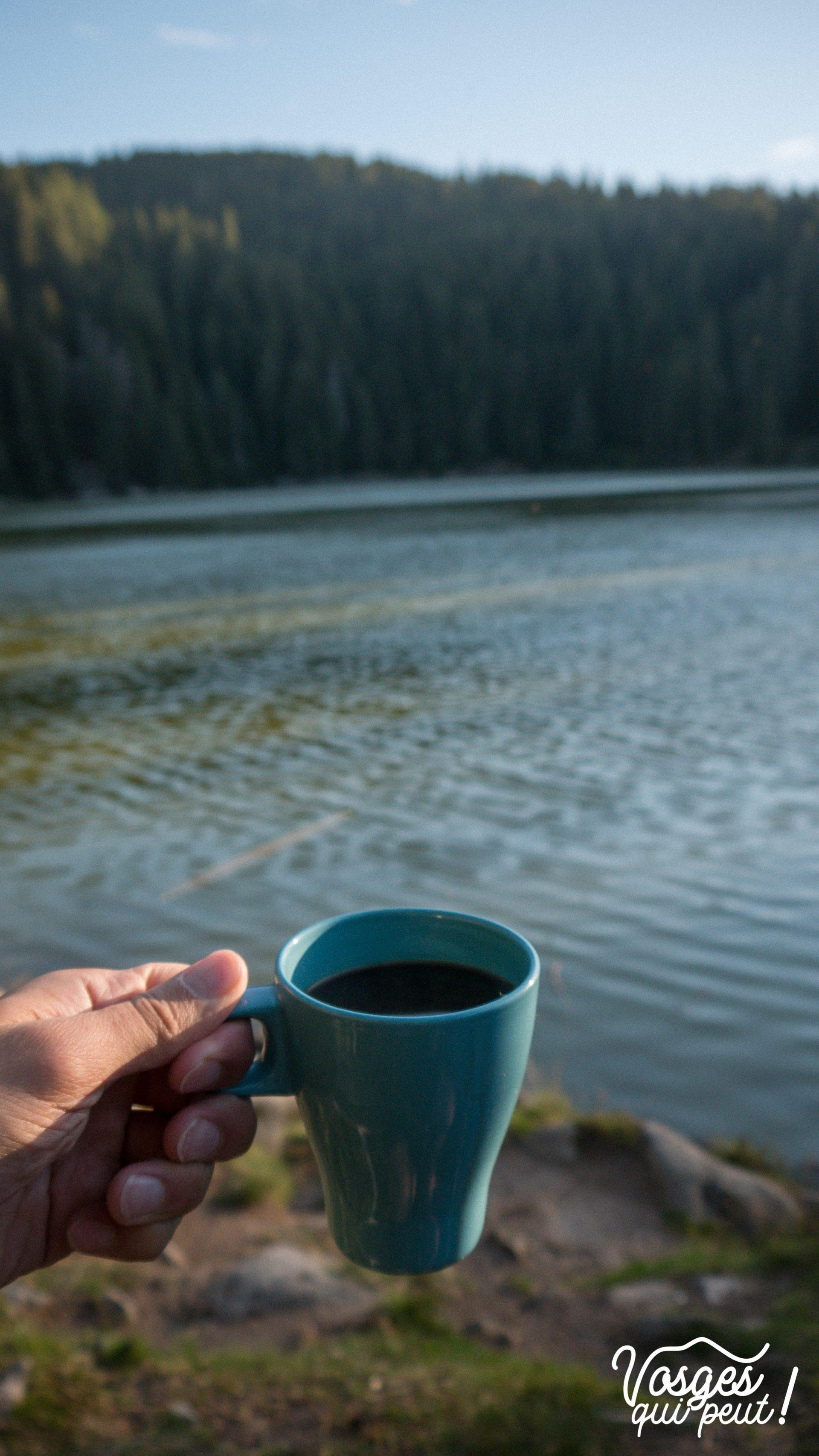 Une main tient une tasse de café sur les bords du lac Vert dans les Vosges